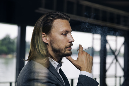 Side view at young businessman enjoying his cigar on a break
