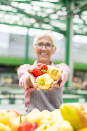 Portrait of senior woman sells organic vegetable on market Stock Photo - 107910839