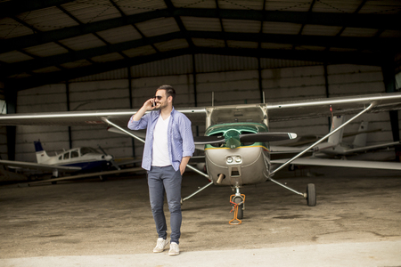 Young handsome young pilot checking airplane in the hangar and using mobile phone