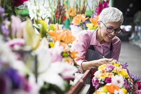 Charrming senior woman arranges flowers on local market