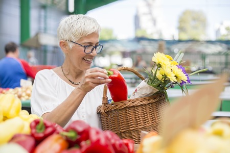 Portrait of good-looking senior woman wearing glasses buys pepper on market