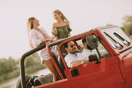 Happy friends having fun in convertible car at vacation by river Stockfoto - 108018920