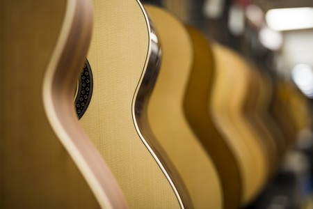 Close up view at acoustic guitars in row in music shop