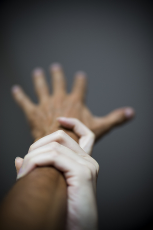 Studio shot of woman holding male hand in the act of violence