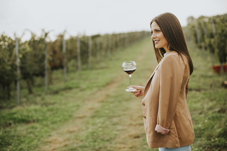 Vintner woman tasting red wine from a glass in a vineyard