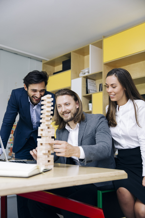 Team of young business people build a wooden construction in the office Banco de Imagens