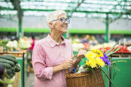 Portrait of senior woman holding basket with bouquet of flowers on market