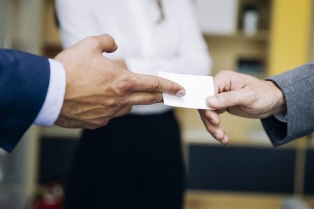 Close-up van ondernemers uitwisselen van visitekaartje op kantoor Stockfoto