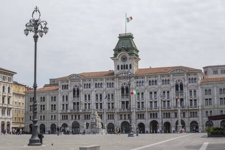 TRIESTE, ITALY - JULY 1, 2018: Unidentified people by Trieste City Hall at Piazza Unita dItalia in Italy. It is the largest seafront square in Europe.