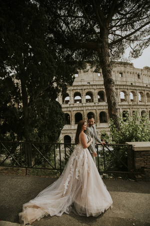 View at bride and groom wedding posing in front of Colosseum, Rome, Italy