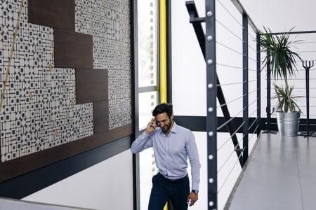Joven empresario hablando por teléfono móvil y escalada en las escaleras en la oficina moderna Foto de archivo - 109065107