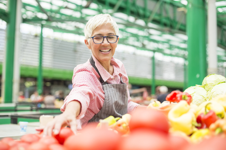 Portrait of senior woman sells organic vegetable on market Stock Photo - 109087197
