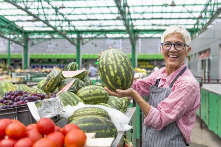 Portrait of senior woman sells watermelon on market Stock fotó