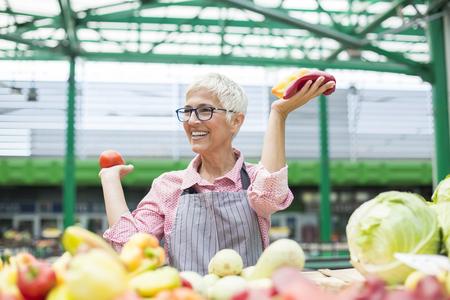 Portrait of senior woman sells organic vegetable on market Stock Photo