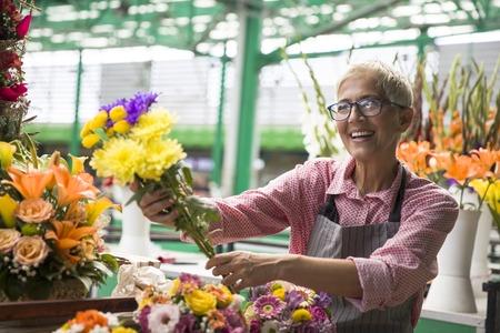 Charrming senior woman sales flowers on local market