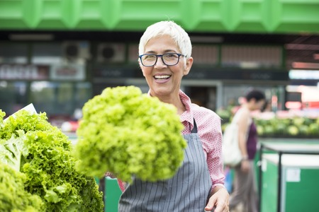 Portrait of senior woman sells lettuce on marketplace