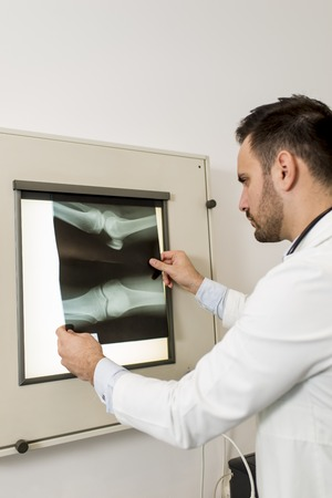 Male doctor looking at x-ray radiography at medical clinic