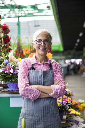 Portrait of charrming senior woman sales flowers on local market