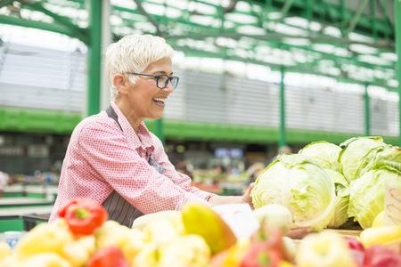 Portrait of senior woman sells organic vegetable on market Stock Photo - 109330926