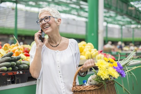 Portrait of senior woman buying on market,  holding basket with flowers and using mobile phone