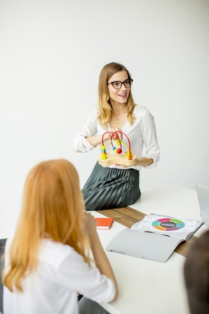 Young woman presenting didactic toys in the office Stock Photo
