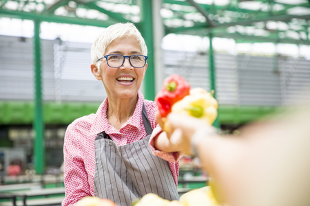 Portrait of good-looking senior woman wearing glasses sells pepper on market Stock Photo
