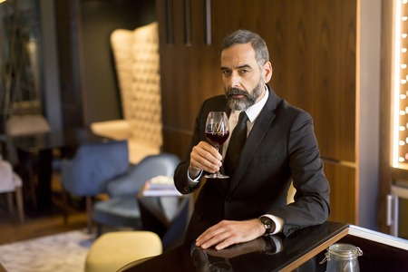 Portrait of senior handsome man drinking red wine
