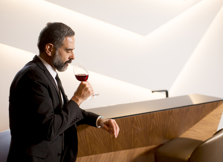 Handsome mature man tasting red wine from the wineglass