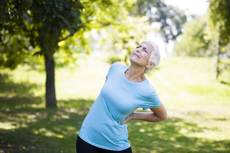Senior fitness woman rubbing the muscles of her lower back. Back pain