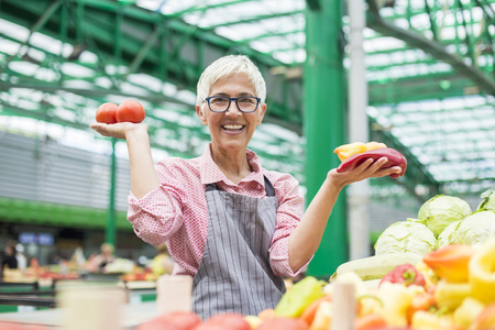Portrait of senior woman sells organic vegetable on market Archivio Fotografico