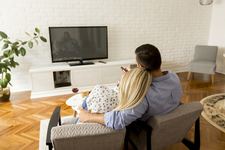 Rear view of couple watching television in living room Stockfoto