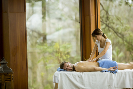 Handsome young man having relax massage in the spa Standard-Bild