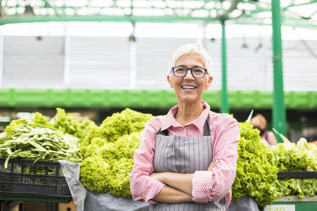 Portrait of good-looking senior woman standing at green market