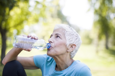 Senior woman rests and drinks water after workout in the park Stockfoto