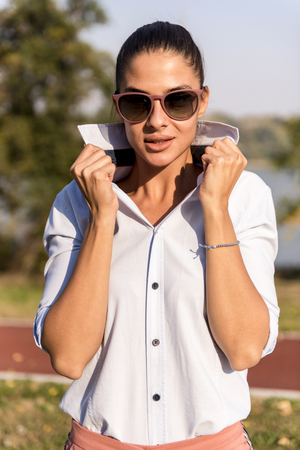 Portrait of beautiful woman wearing sunglasses posing at outdoor on sunny day