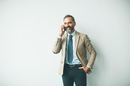 Hübscher reifer Geschäftsmann, der im Büro mit dem Handy spricht