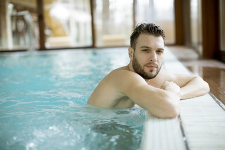 Handsome young man relaxing in hot tub in spa