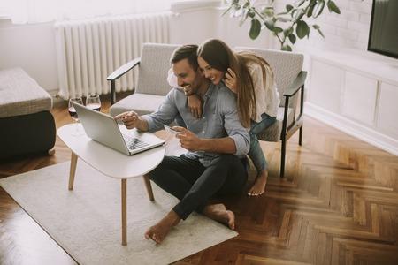 Pareja alegre buscando internet y compras en línea en la sala de estar en casa