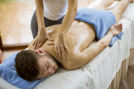 Handsome young man having relax massage in the spa Stock Photo