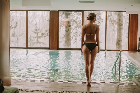 Pretty young woman getting into water at swimming pool in spa center