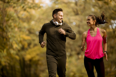 Young couple jogging together in autumn park Stock Photo