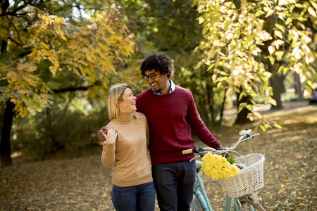 Young multiracial couple walking through park and  pushing a bicycle