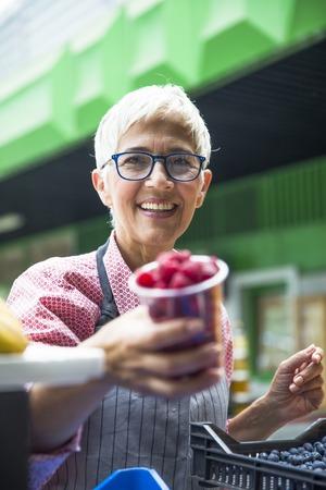 Portrait of senior woman sells raspberries on market