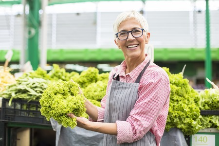 Portrait of senior woman sells lettuce on marketplace
