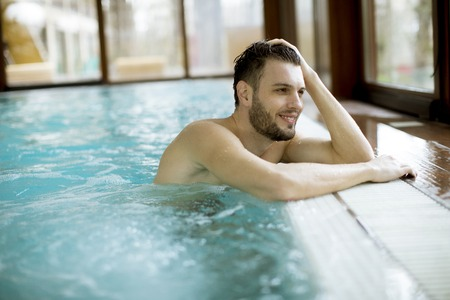 Handsome young man relaxing in hot tub in spa Stok Fotoğraf - 110722504