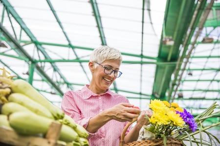 Portrait of senior woman buying on market