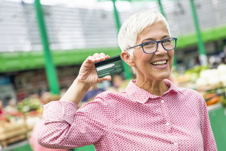 Portrait of senior woman holds credit card on market Stock Photo