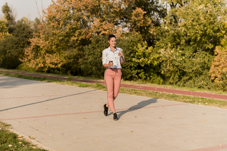 Happy young woman with coffee listening music on smartphone and walking on promenade ta beautiful autumn day