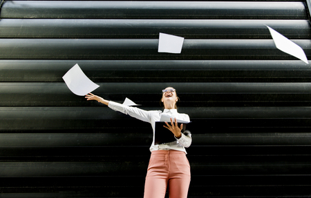 Portrait of young businesswoman in business clothing throwing up paper documents outdoor