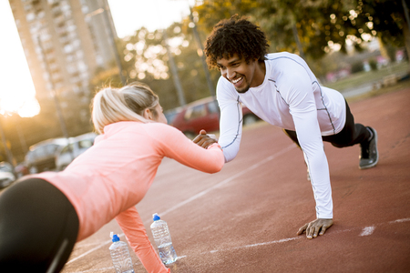 Smiling multiracial couple doing workout outdoor Stock Photo
